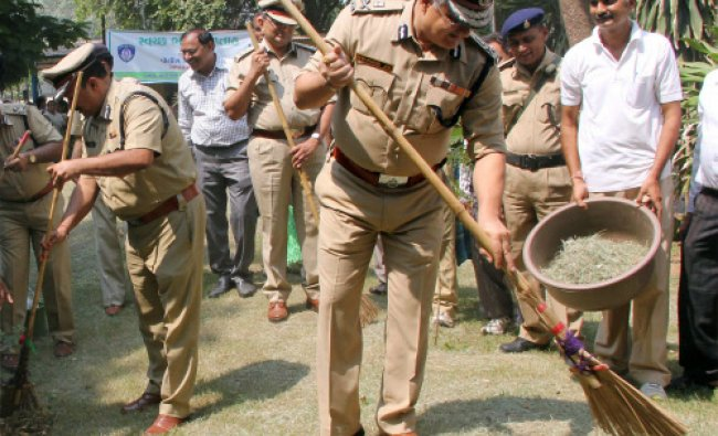 Police Commissioner Shivanand Jha sweeps the office premises as he participates in the...