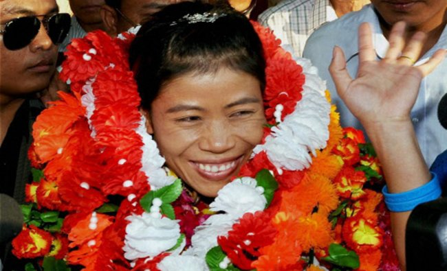 Asian Games gold medalist boxer Mary Kom is greeted with garlands upon her arrival...