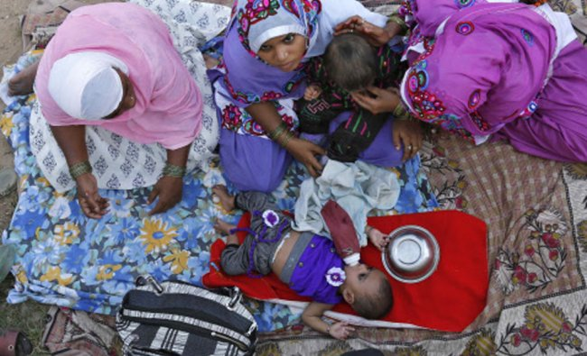 Muslim women feed their children as they wait to offer a special prayer at the shrine...