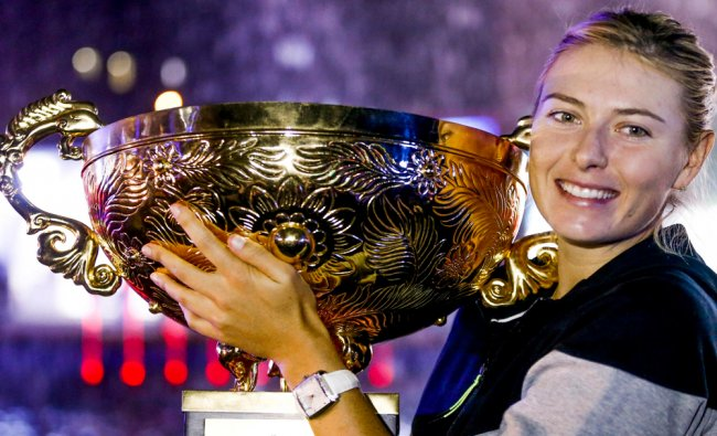 Maria Sharapova holds her trophy after she won the woman\'s singles final match at the China Open...