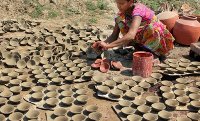 A woman colors earthen pots called as \'Diya\' ahead of the Diwali festival in Ahmedabad...