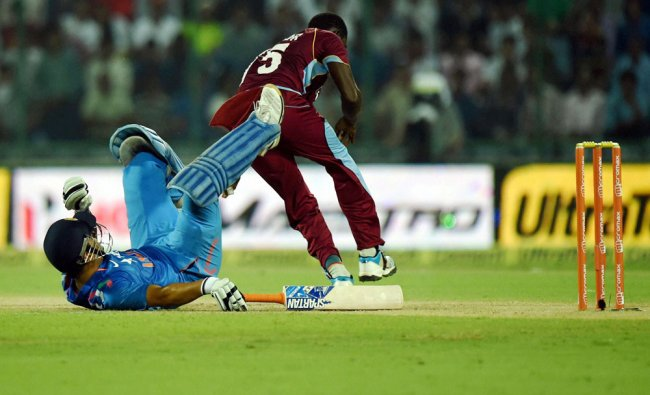 India\'s skipper MS Dhoni falls on the ground during the 2nd ODI cricket match against West Indies...