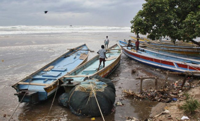 Boys walk on fishing boats by the shore before being evacuated at Vizag...
