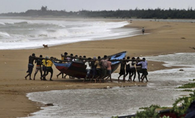 Fishermen move a boat away from the coast following a cyclone warning in Ganjam districts...