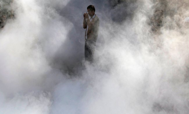 A man puts on his glasses in a street being fumigated by municipal workers in Srinagar...