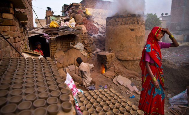 An Indian woman walks past clay lamps kept for drying before being put in a kiln to hard...