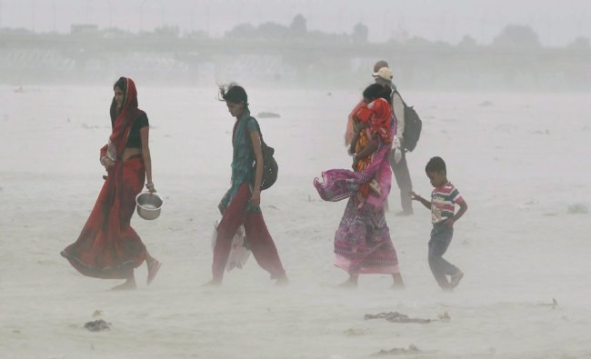 People walk through a dust storm on the bank of river Ganga...