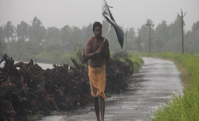 A man struggles with an umbrella in strong winds and rain caused by Cyclone Hudhud in Gopalpur...