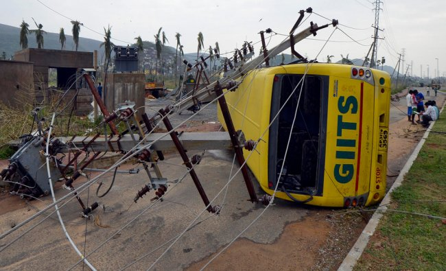 Power lines and a passenger bus are seen after being damaged by strong winds caused by Cyclone...