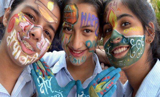 School children paint their faces during Diwali celebrations...