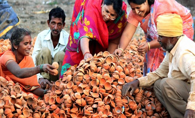 Woman buying earthen lamps at a market ahead of the Diwali festival...