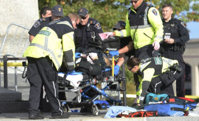 Police and paramedics tend to a soldier shot at the National Memorial near Parliament Hill...