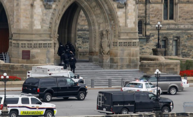 Armed RCMP officers head in to Centre Block on Parliament Hilll following a shooting incident...