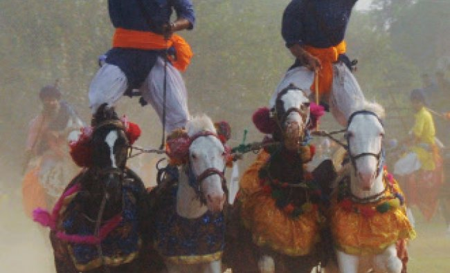 Sikh religious warriors display their skills as they ride