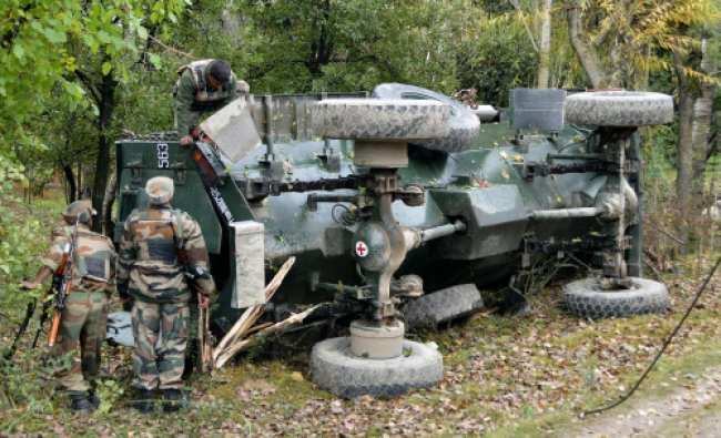 Army Personnel inspecting their damaged vehicle
