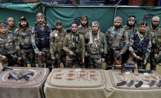 Army soldiers display arms and ammunition recovered