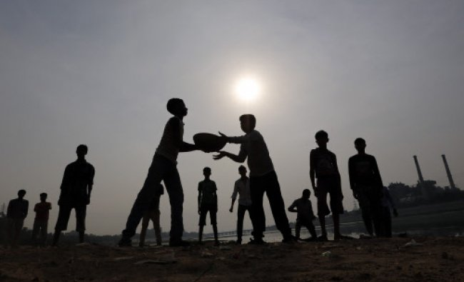 Local boys carry a container filled with soil to use it to level the parts of the Sabarmati...