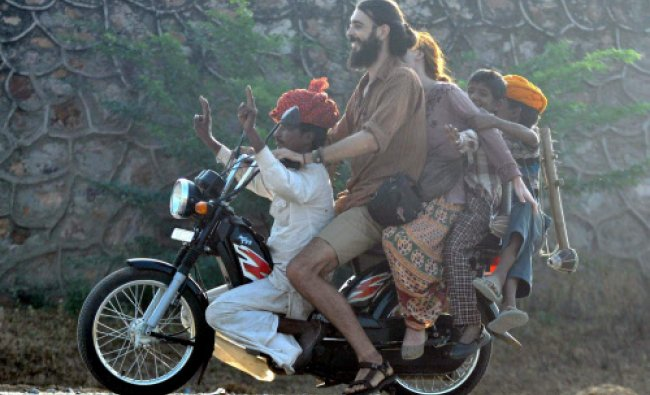 Foreign tourists enjoy ride with the locals during Pushkar Camel Festival...