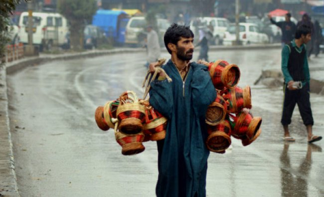 A vendor carrying Kangrir, a traditional fire-pot used by the people to keep themselves...