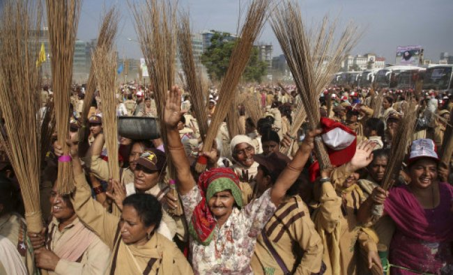 Volunteers of the sect, Dera Saccha Sauda, raise brooms as they arrive for a cleanliness drive...