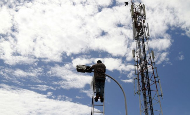 A technician from Cochin Municipal Corporation repairs a street lamp post at a road side...