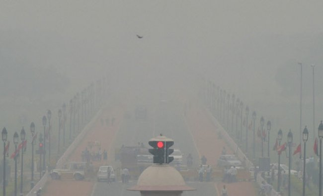 Vehicles ply at Rajpath as fog covers it in New Delhi...