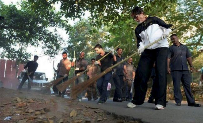Bollywood megastar Amitabh Bachchan sweeps in a stree during a cleanliness drive as a part...