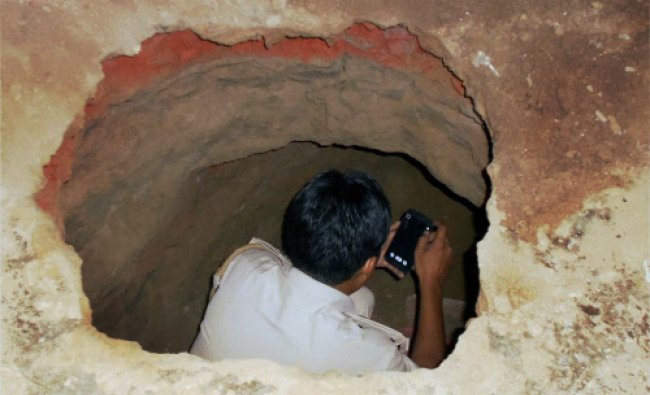 A police man investigates the tunnel dug up by the robbers in Gohana bank heist, in Sonipat...