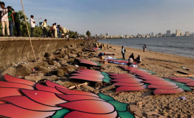 BJP workers arrange the cut-outs of party symbol (lotus) to decorate the boats at the Marine...