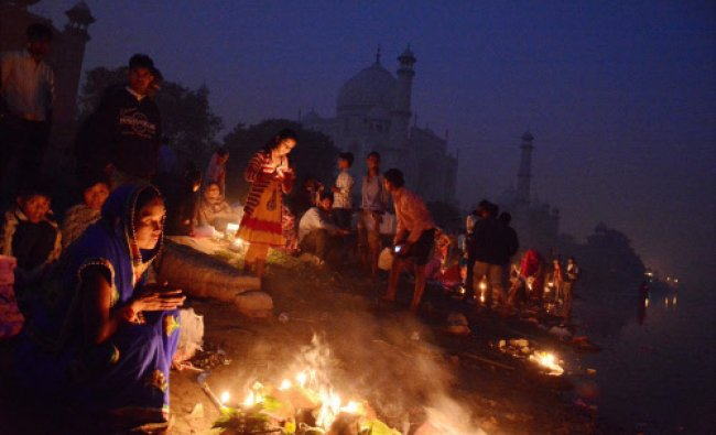 Devotees wait for the Sun to offer prayers, during Chhath Puja festival in Agra...