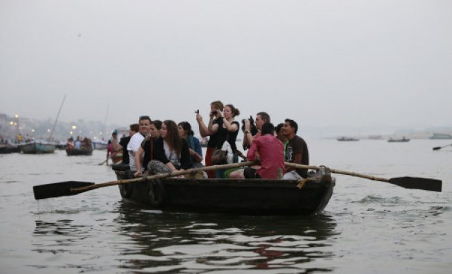 Tourist take pictures from a boat as people bath in the Ganges river in Varanasi...