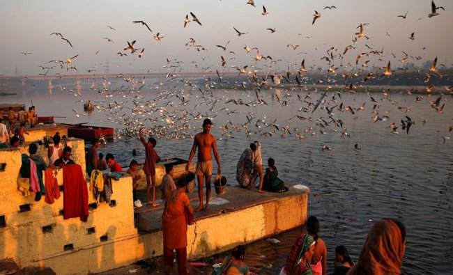 Hindu devotees prepare to take a dip in the waters of the river Yamuna...