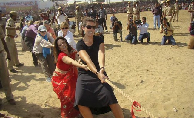 Foreign tourists participate in a \'Tug of War\' competition at the Pushkar Fair...