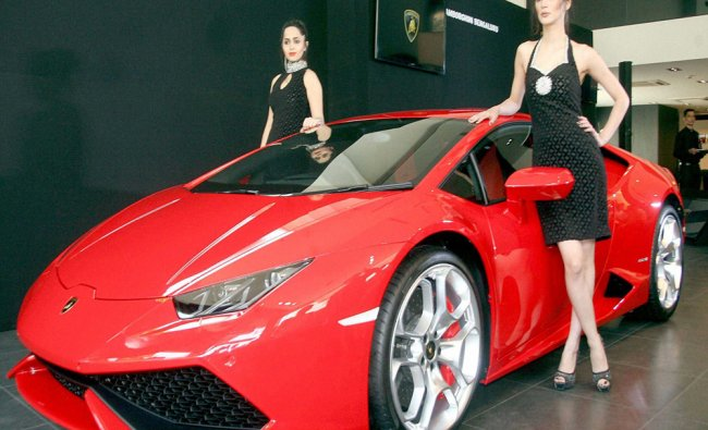Models pose with a car during the inauguration of the Lamborghini showroom...
