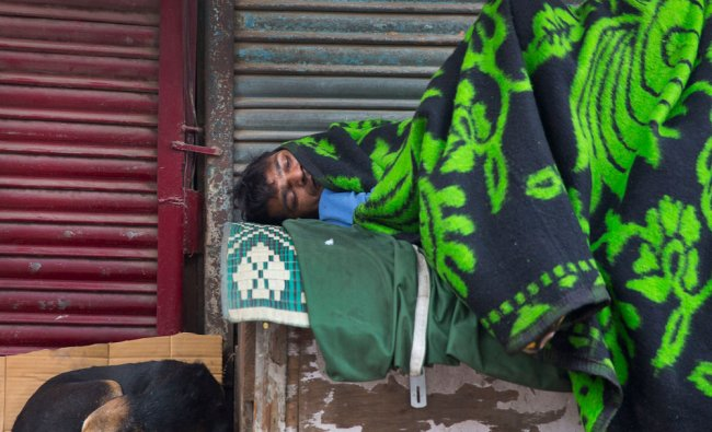 A stray dog and a homeless sleep in front of a closed shop on a cold morning in New Delhi....