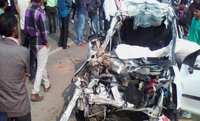 A car lies completely wrecked after an accident on the Kosamba highway which left five...