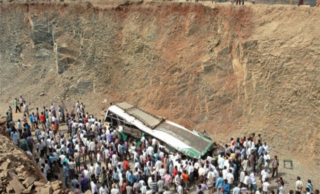People gather near the ill-fated bus that fell downhill...