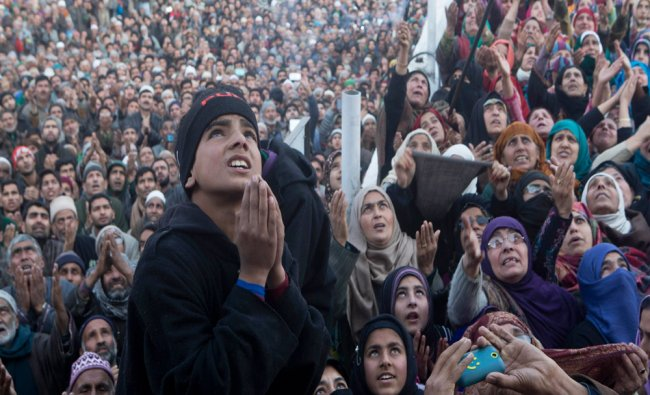 Kashmiri Muslims pray as they look towards a relic...