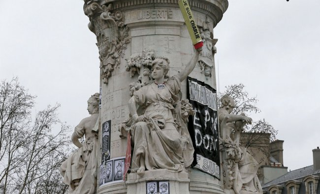 The statue in Paris is seen featured with a giant cardboard pencil reading I am Charlie...