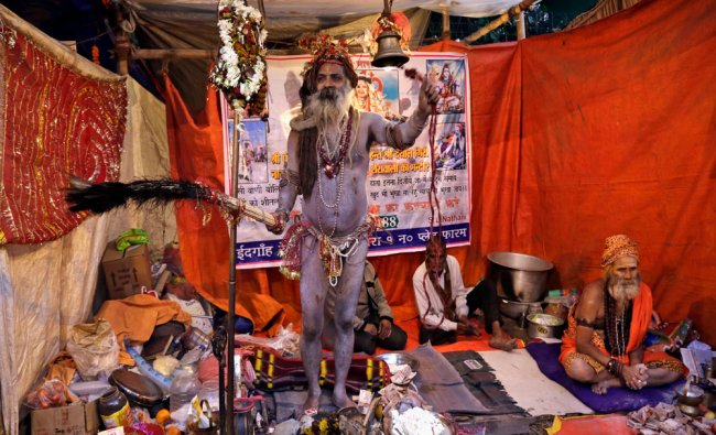 A Naga sadhu rings a bell to attract pilgrims to receive offerings at his resting place...