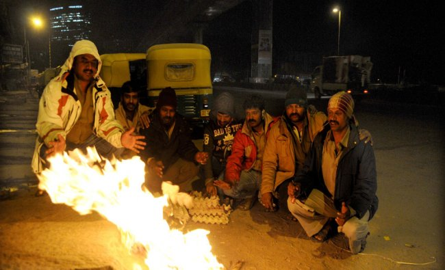 Auto rickshaw Drivers warm their hands on a fire as they wait for the night passengers...