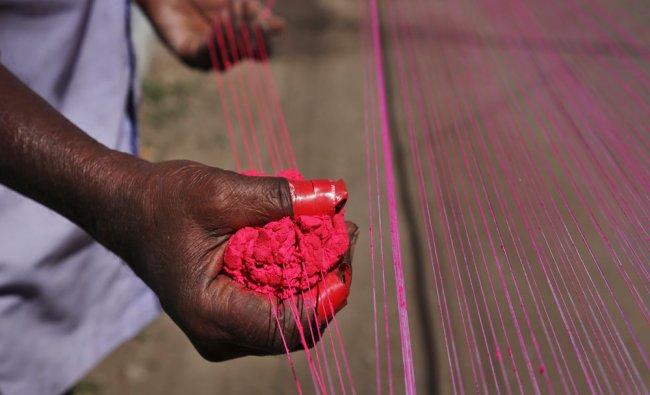 An Indian worker prepares kite strings ahead of the Hindu festival of Makar Sakranti...