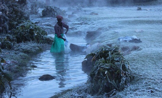 A washerman washes clothes in the chilling stream of water as the temperature dips in Ooty...