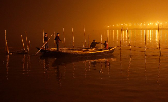 Boys tie their boats as fog covers the banks of the Yamuna river on a cold evening in Allahabad...
