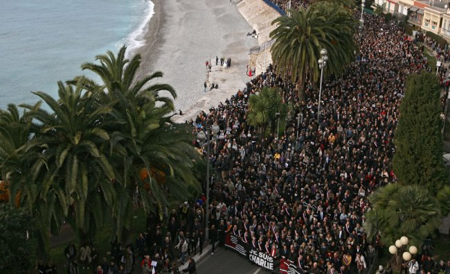 People take part in a silent procession to honor the 17 victims who died...