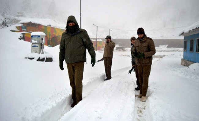 Police officials walk on a snow-covered road at Qazigund as Srinagar- Jammu National Highway