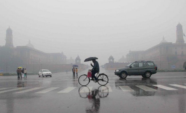 A man pedals his bicycle while holding an umbrella at Vijay Chowk as it rains in New Delhi