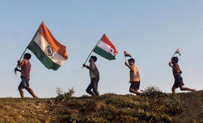 Children run with the tricolour ahead of Republic Day, on the banks of the Brahmaputra River...