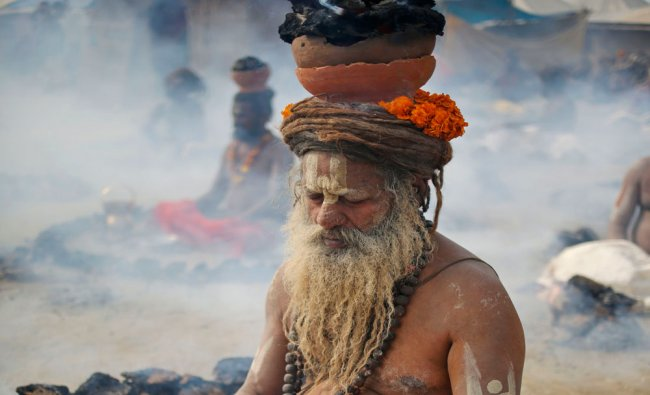 A Sadhu performs a ritual by burning dried cow dung cakes in earthen pots overhead for salvation.