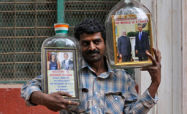 Indian bottle artist Gowda displays glass jars containing welcome messages for U.S. President...